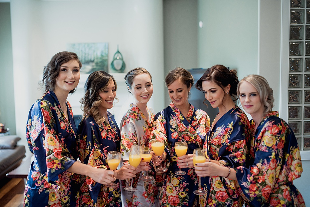 bride-bridesmaids-toasting-orange-juice-in-flower-robes